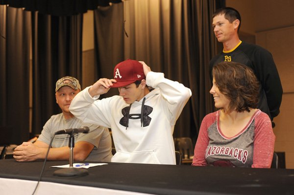 Aaron Kincaid, center, Prairie Grove senior, signs Thursday to play baseball for the University of Arkansas while his father, Chris, left; mother, Bonnie; and Prairie Grove coach Mitch Cameron watch during a ceremony at the school. Kincaid will join fellow Tiger Jalen Beeks on the Razorback roster.