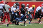 Campers participate in drills Monday during football camp at the University of Arkansas.
