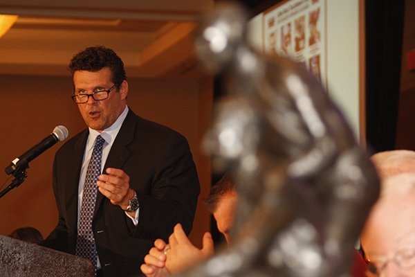 The Broyles Award, given each year to the outstanding assistant coach in college football, sits in the foreground while David Bazzel gives the opening remarks at the first Touchdown Club luncheon of 2013.