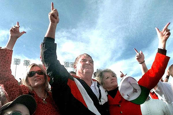 "Texas Tech coach Spike Dykes, center, flanked by his wife, Sharon, right, and daughter, Bebe Petree, give the ""guns up"" salute during the university song after beating Oklahoma 38-28 in Lubbock, Texas, Saturday, Nov. 20, 1999. After 13 seasons, Dykes announced his retirement following the game. (AP Photo/LM Otero)"