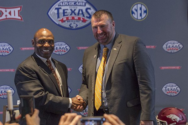 Texas coach Charlie Strong, left, and Arkansas coach Bret Bielema shake hands following a press conference at the Westin Galleria hotel Saturday, Dec. 27, 2014 in Houston.