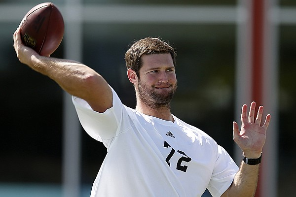 Quarterback Tyler Wilson warms up before the NFL veterans combine football workout, Sunday, March 22, 2015, in Tempe, Ariz. (AP Photo/Rick Scuteri)