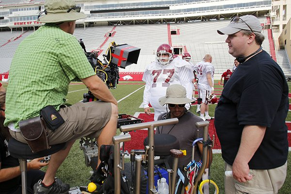 Director David Hunt (right) discusses the camera angle as actor Chris Severio, portraying former University of Arkansas football player Brandon Burlsworth (center), waits to shoot a football sequence at Razorback Stadium in Fayetteville on Wednesday, May 29, 2013.