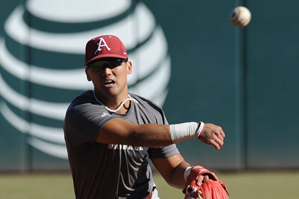 Rick Nomura of Arkansas makes the relay to first Friday, Jan. 29, 2016, during practice at Baum Stadium in Fayetteville.