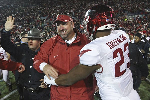 Arkansas linebacker Dre Greenlaw celebrates with coach Brett Bielema after defeating Kansas State 45-23 in the Liberty Bowl 45-23 on Saturday, Jan. 2, 2016, in Memphis.