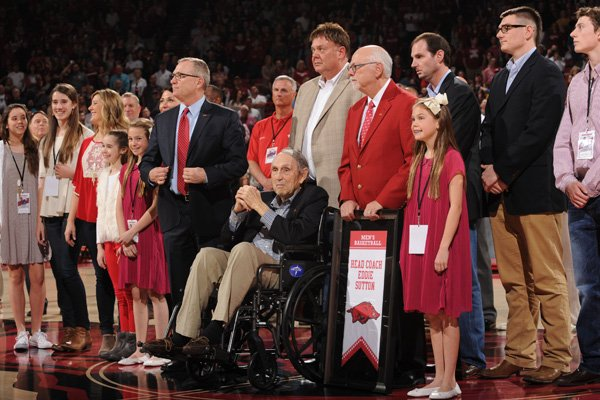 Former Arkansas coach Eddie Sutton (center) watches Saturday, Feb. 20, 2016, as he is surrounded by family, administrators and former players as a banner honoring him is dedicated in Bud Walton Arena during a ceremony at halftime in Fayetteville. Sutton coached Arkansas from 1974 to 1985 and led the Razorbacks to the Final Four and a third-place finish in 1978.
