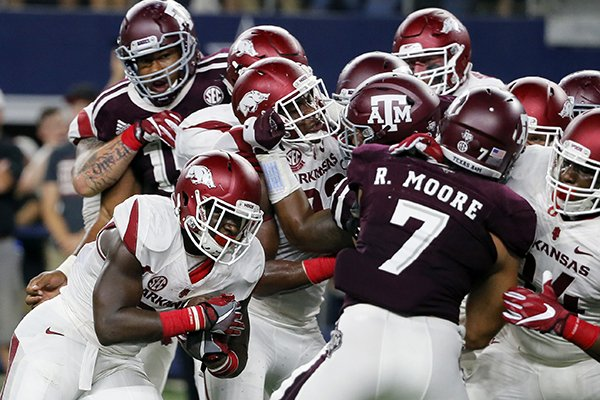 Arkansas running back Rawleigh Williams III, bottom left, attempts to run the ball against Texas A&M linebacker Richard Moore (7) in the first half of an NCAA college football game, Saturday, Sept. 24, 2016, in Arlington, Texas. (AP Photo/Tony Gutierrez)