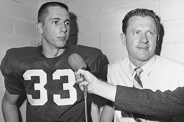 Bobby Burnett, left, University of Arkansas tailback who scored the winning touchdown in the fourth period of the Cotton Bowl game, and his coach Frank Broyles are a happy pair as they chat in the locker room after the game. Arkansas defeated Univ. Nebraska 10-7 in the Cotton Bowl at Dallas, Texas, January 1, 1965. (AP Photo/Ted Powers)