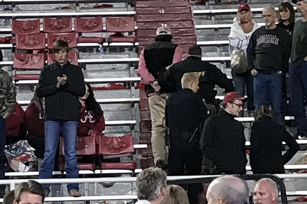 A fan is escorted by police out of Razorback Stadium following Arkansas' loss to Alabama on Saturday, Oct. 8, 2016, in Fayetteville.