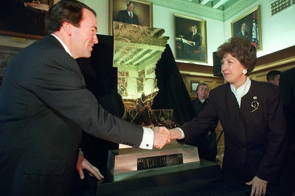 Arkansas Gov. Mike Huckabee, left, shakes hands with Louisiana Lt. Gov. Kathleen Blanco after they unveiled The Boot trophy at Huckabee's office in Little Rock on Wednesday, Nov. 27, 1996.