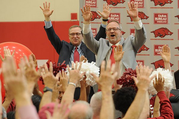 Arkansas women's basketball coach Mike Neighbors, right, and athletics director Jeff Long lead a Hog call during Neighbors' introductory press conference on Tuesday, April 4, 2017, in Fayetteville.