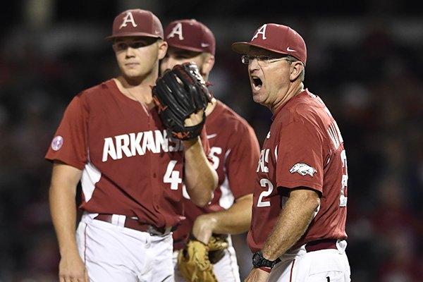 Arkansas coach Dave Van Horn, right, calls for a relief pitcher as he visits the mound to talk with pitcher Kevin Kopps (45) in the third inning of an NCAA college baseball regional tournament game against Missouri State in Fayetteville, Ark., Sunday, June 4, 2017. (AP Photo/Michael Woods)