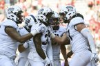 TCU running back Sewo Olonilua (33) celebrates with teammates Lucas Niang, left, and Cole Hunt, right, after scoring a touchdown against Arkansas in the second half of an NCAA college football game in Fayetteville, Ark., Saturday, Sept. 9 2017. (AP Photo/Michael Woods)