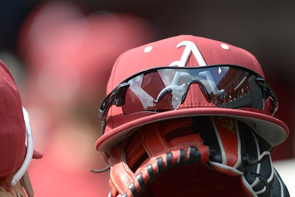 An Arkansas baseball hat sits atop a glove during a game between the Razorbacks and Kent State on Sunday, March 11, 2018, in Fayetteville.