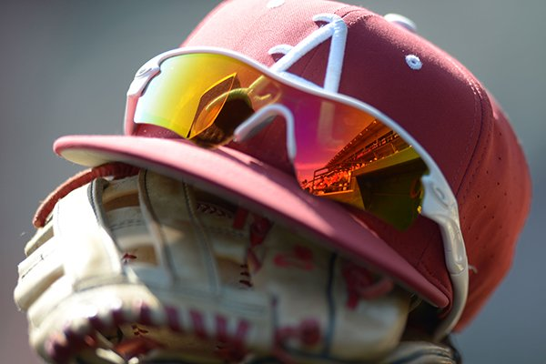 An Arkansas hat and glove sit in the dugout prior to a game against Louisiana-Monroe on Wednesday, April 4, 2018, in Fayetteville.