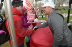 Arkansas football coach Chad Morris (right) shakes hands with David Carlton, a former player from Tulsa, Okla., his wife, Rebekah, and their 1-year-old daughter, Kinsley, Saturday, April 14, 2018, during the annual Hogfest, a fan appreciation day in The Gardens on the University of Arkansas campus in Fayetteville.