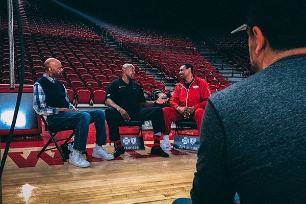 """From left to right, former Arkansas basketball players Ron Brewer, Sidney Moncrief and Marvin Delph speak while filmmaker Christopher Hunt, foreground, watches on Wednesday, Feb. 28, 2018, at Bud Walton Arena in Fayetteville. The """"Triplets,"""" as the trio is known, were interviewed for a documentary film about their former coach, Eddie Sutton."""
