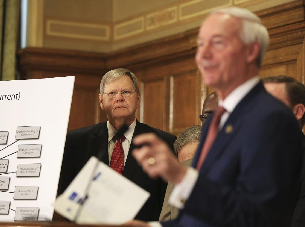 Mike Carroll (left), chairman of Gov. Asa Hutchinson's Transformation Advisory Board, appears with Hutchinson at  the state Capitol on Wednesday as Hutchinson announces his state government reorganization plan.