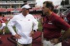 Arkansas coach Chad Morris (left) and Alabama coach Nick Saban speak prior to a game Saturday, Oct. 6, 2018, in Fayetteville.