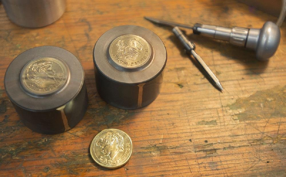 A freshly minted Lannister coin is shown next to its dies at the Shire Post Mint in Springdale. The company has started a Kick- starter campaign to fund a new run of coins based on George R.R. Martin's Game of Thrones.