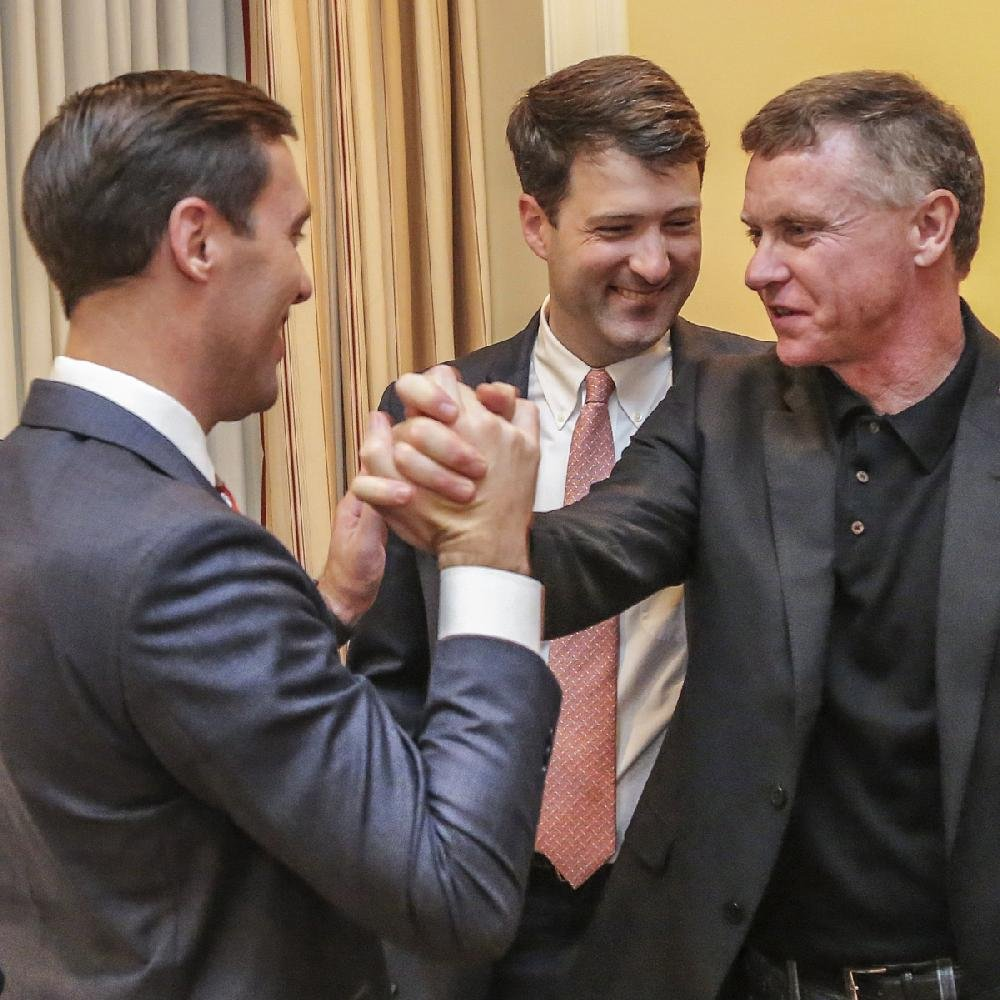 Nate Steel (left), legal counsel for Driving Arkansas Forward, celebrates the gambling proposal's passage Tuesday night with Tony Holden (right) and Alex Gray.