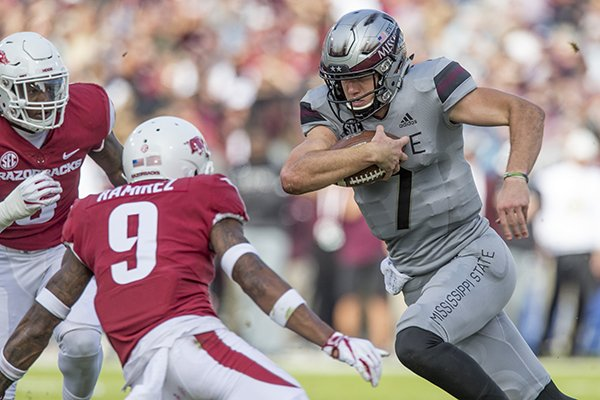 Mississippi State quarterback Nick Fitzgerald carries the ball while Arkansas defenders Santos Ramirez (9) and De'Jon Harris (8) try to tackle him during a game Saturday, Nov. 17, 2018, in Starkville, Miss.