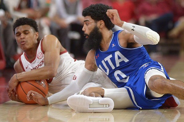 Arkansas guard Jalen Harris (left) and Texas-Arlington guard Brian Warren vie for a loose ball Friday, Nov. 23, 2018, during the first half of play in Bud Walton Arena in Fayetteville.
