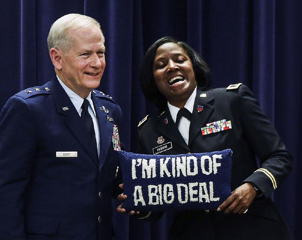 Maj. Gen. Mark H. Berry and Col. Erica Ingram react Thursday after Berry presented her with this pillow during her promotion ceremony at Camp Robinson in North Little Rock.