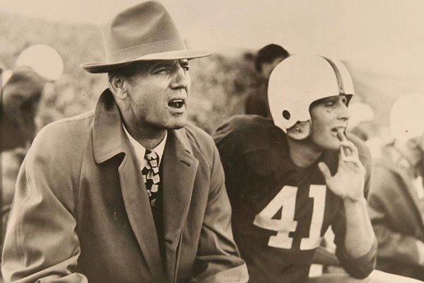 """Arkansas coach John Barnhill and player Buddy Sutton watch from the sidelines during an undated game at War Memorial Stadium in Little Rock in 1949. The photo is the cover of the new collector's book """"Footsteps Have Trod: 125 Seasons of Arkansas Football."""""""