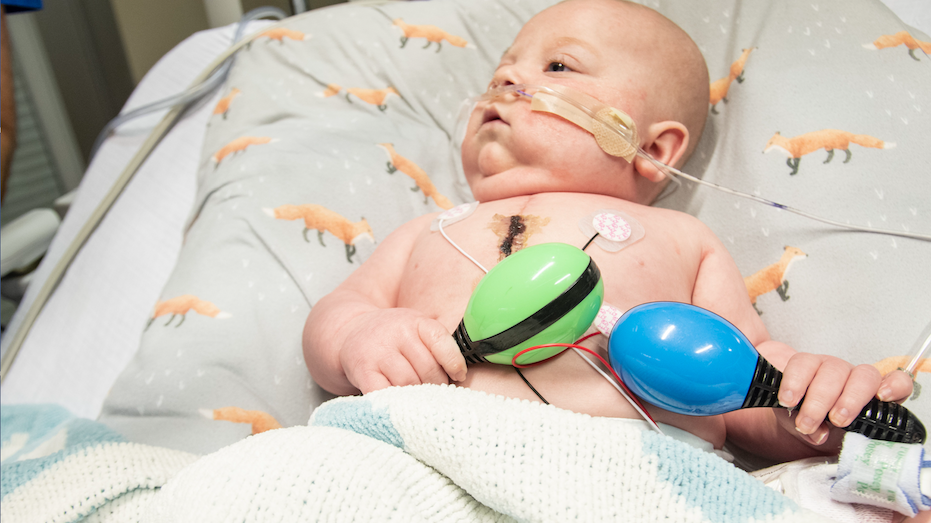 Arkansas Democrat-Gazette/CARY JENKINS Five month old Paxton Allen at Arkansas Children's Hospital practices his grip during a music therapy session