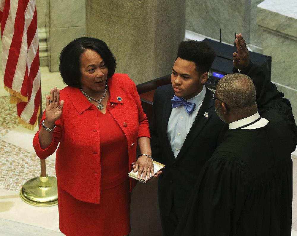 New Pulaski County Circuit and County Clerk Terri Hollingsworth,  joined by her son Joshua Davis, is sworn in Tuesday by Judge  Wendell Griffen during a ceremony at the Pulaski County Courthouse.