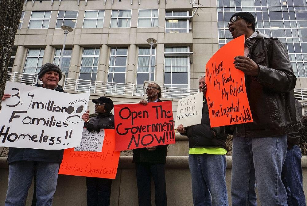 Toney Orr of Little Rock leads chants on Friday as people protest the partial federal government shutdown outside the Victory building, which houses the Little Rock offices of U.S. Sens. Tom Cotton and John Boozman.