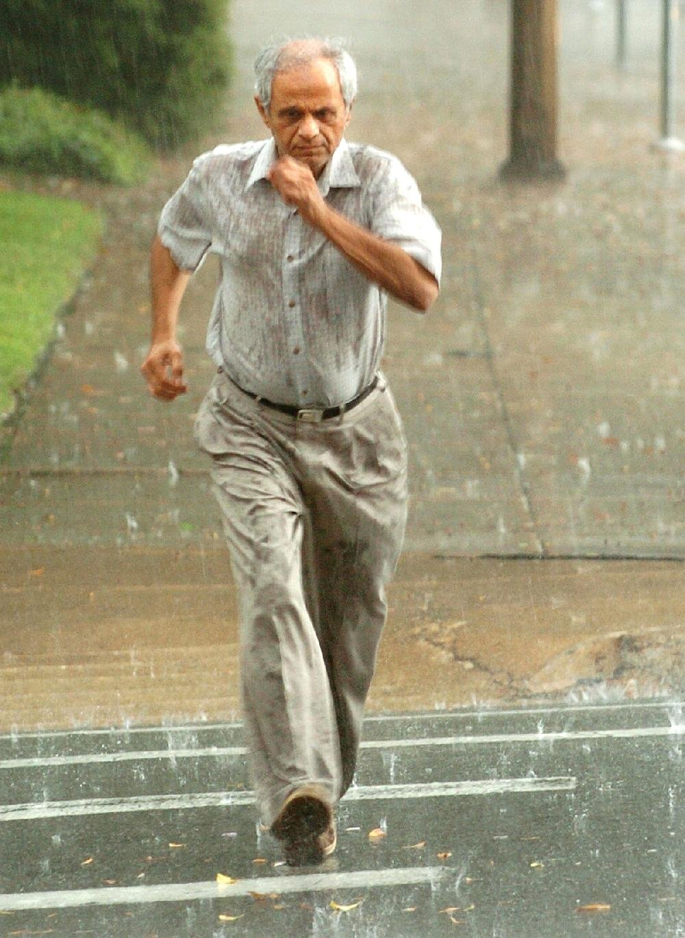 """Imran Bohra runs for cover during a sudden thunderstorm in downtown Little Rock in this October 2010 feature photo. An attorney who specializes in housing matters calls Bohra a """"slumlord on steroids"""" for his treatment of people who rent property from him."""