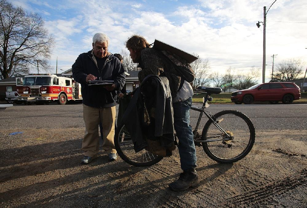 Volunteer Victor Moya jots down information from Kevin Teer while conducting a count of homeless people Thursday on Roosevelt Road in Little Rock. Moya and other volunteers assisted providers of homeless services in the biennial census in central Arkansas.