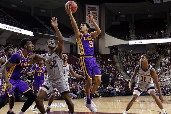 LSU guard Tremont Waters (3) shoots over Texas A&M forward Josh Nebo (32) as LSU forward Kavell Bigby-Williams, left, and Texas A&M guard Wendell Mitchell, right, watch during the second half of an NCAA college basketball game Wednesday, Jan. 30, 2019, in College Station, Texas. (AP Photo/Michael Wyke)