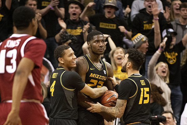 Missouri's Jeremiah Tilmon, center, holds on the ball as teammates Jordan Geist, right, and Javon Pickett, left, celebrate after they defeated Arkansas 79-78 during an NCAA college basketball game Tuesday, Feb. 12, 2019, in Columbia, Mo. (AP Photo/L.G. Patterson)