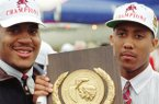 Arkansas basketball players Corliss Williamson (left) and Scotty Thurman pose with the NCAA championship trophy at Drake Field in Fayetteville on Tuesday, April 5, 1994.