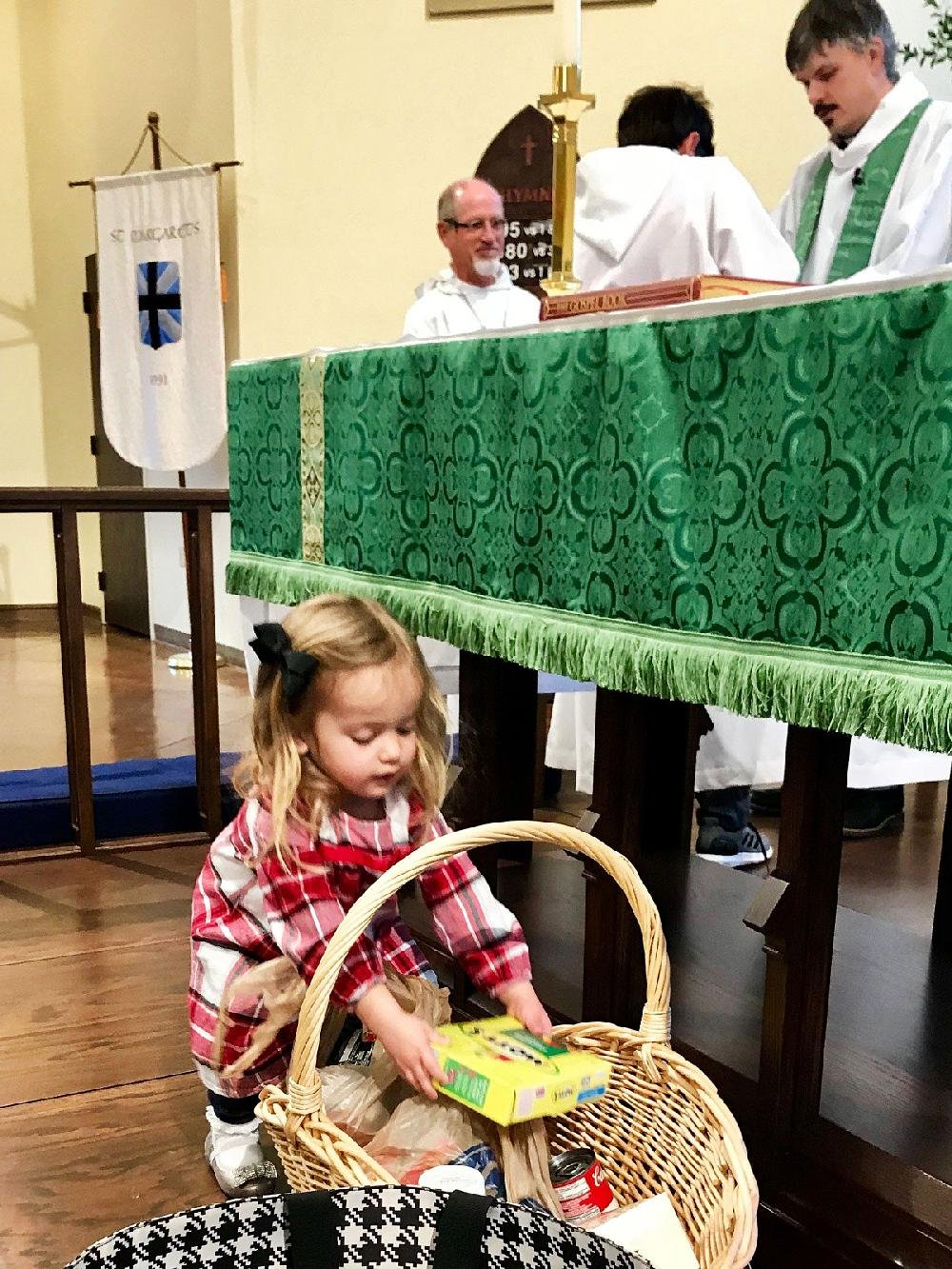 A young parishioner at St. Margaret's Episcopal Church in Little Rock makes a food contribution to the church's offering basket