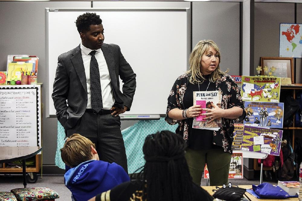 Assistant Superintendent Gregory Hodges of the Jacksonville/North Pulaski School District waits as Pinewood Elementary fifth-grade teacher Susan Fincher explains to her class the lesson plan Hodges will teach them. Hodges was rewarding Fincher with an afternoon off for her reliability.