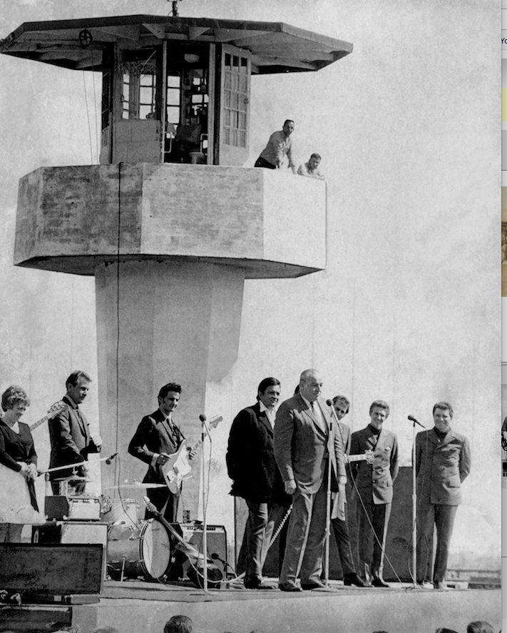 Arkansas Gov. Winthrop Rockefeller (at microphone) and Johnny Cash (behind Rockefeller), are beneath a guard tower at Cummins Prison in 1969. Cash performed a show for the inmates. (Democrat-Gazette file photo)