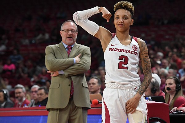Arkansas guard Alexis Tolefree flexes while coach Mike Neighbors looks on during a second round WNIT game against UAB on Sunday, March, 24, 2019, in Fayetteville.