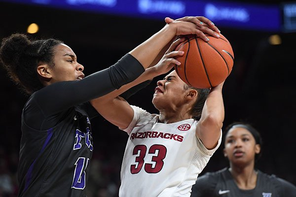 Arkansas' Chelsea Dungee has a shot blocked by TCU's Jayde Woods during a third round WNIT game Thursday, March 28, 2019, in Fayetteville.