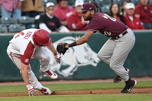 Arkansas' Trevor Ezell is tagged by UALR third baseman Garrett Scott during a game Tuesday, April 2, 2019, in Fayetteville.