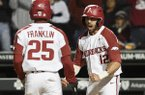Arkansas catcher Casey Opitz (12) celebrates with outfielder Christian Franklin after both players scored a run during the sixth inning of a game against Mississippi State on Thursday, April 18, 2019, in Fayetteville.
