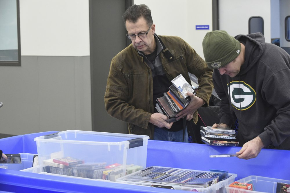 In this April 12, 2019, photo Ron Edquist, left, of Kenosha, peruses a bin full of DVDs, video games and Blu-ray Discs at the Goodwill outlet store in Sturtevant, Wis. (Adam Rogan/The Journal Times via AP)