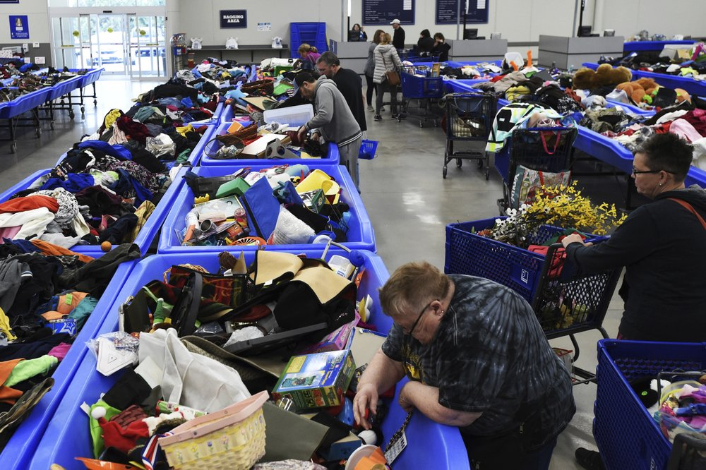 In this April 12, 2019, photo shoppers at Goodwill Industries' outlet store find extra deals in rows upon rows of assorted bins in Sturtevant, Wis. (Adam Rogan/The Journal Times via AP)