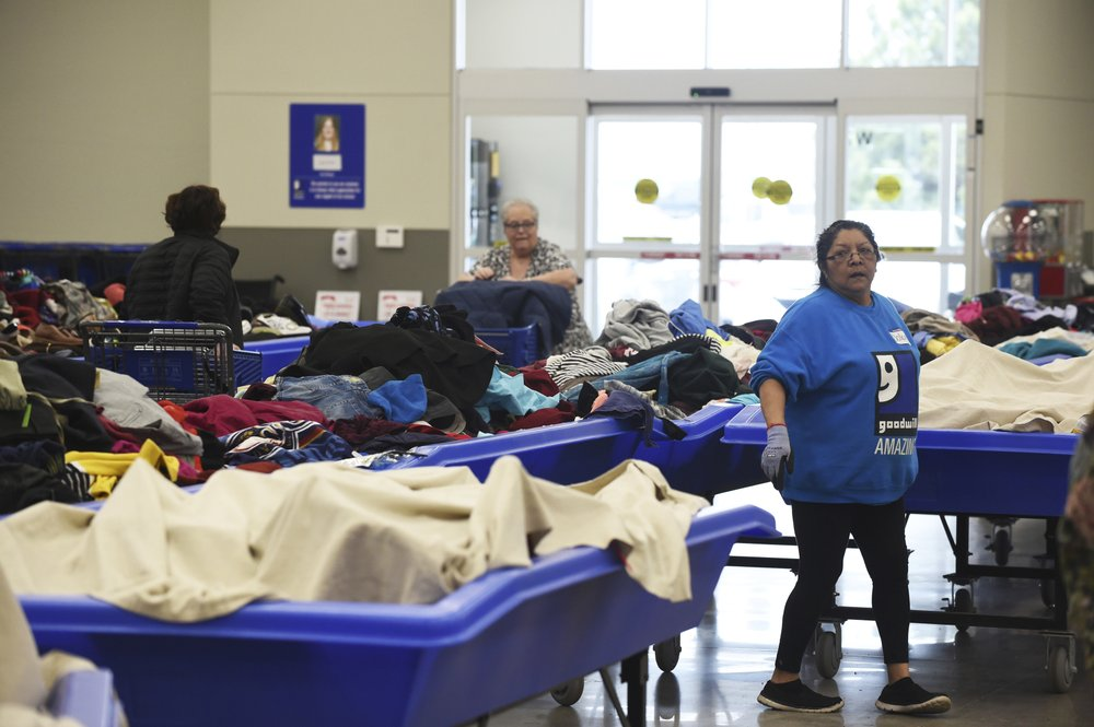 In this April 12, 2019, photo a employee lines up bulk bins full of unsold products to be unveiled at Goodwill's outlet store in Sturtevant, Wis. (Adam Rogan/The Journal Times via AP)