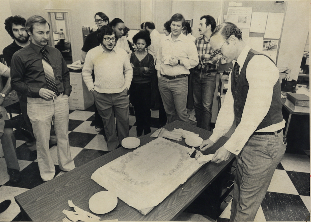 Walter Hussman, far right, cuts a cake on Nov. 1, 1980, as newsroom employees look on. (Arkansas Democrat-Gazette file photo)
