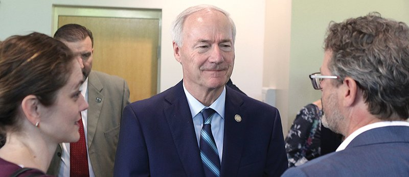 The Sentinel-Record/Richard Rasmussen DISCUSSION: Governor Asa Hutchinson speaks with Amanda Ashworth of Fayetteville, left, and Phillip Owens, right, of Booneville at the Arkansas Rural Economic Development Conference at the Hot Springs Convention Center on Wednesday.
