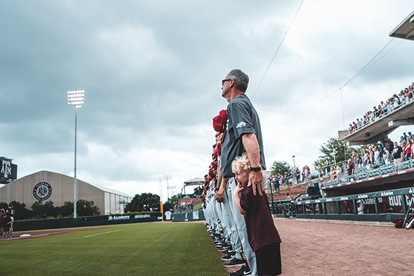 Arkansas coach Dave Van Horn consoles a child during the national anthem prior to a game against Texas A&M on Saturday, May 18, 2019, in College Station, Texas.